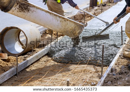 Truck loads of concrete pouring at construction into the concrete at a construction in a sidewalk Foto stock ©
