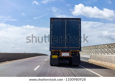 Truck on highway road with blue container, transportation concept.,import,export logistic industrial Transporting Land transport on asphalt expressway with blue sky #1100980928
