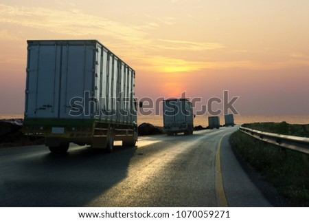 Truck on highway road with container, transportation concept.,import,export logistic industrial Transporting Land transport on asphalt expressway with sunrise sky #1070059271
