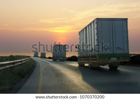 Truck on highway road with container, transportation concept.,import,export logistic industrial Transporting Land transport on asphalt expressway with sunrise sky #1070370200