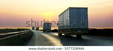 Truck on highway road with container, transportation concept.,import,export logistic industrial Transporting Land transport on asphalt expressway with sunrise sky #1077208466