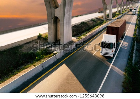 Truck on highway road with red  container, transportation concept.,import,export logistic industrial Transporting Land transport on the asphalt expressway with sunrise sky #1255643098