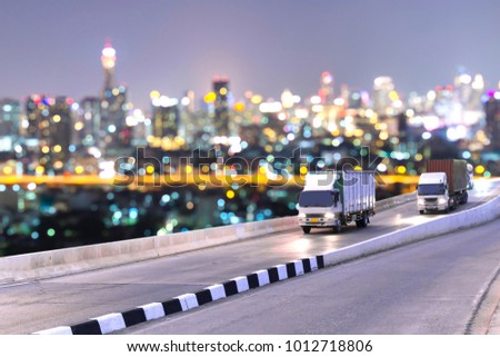 Truck on road container, transportation concept.,import,export logistic industrial Transporting Land transport on the expressway driving to Night City view with bokeh lights #1012718806