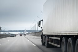 Truck on road. Delivery and shipping concept. Grey cold winter day.