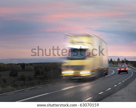 Truck on road in evening with purple sky