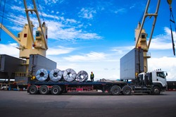 Truck receive steel coils alongside large cargo ship at port