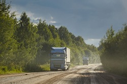 Truck rides on a damp dirt road after rain, against the backdrop of the forest and the rays of the sun