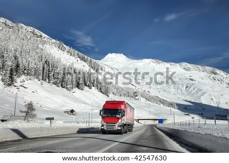 truck running on highway and beautiful snowy mountains on the background