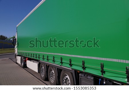 Truck transport. View of the green tarpaulin covering the semi-trailer of the truck. Сток-фото ©