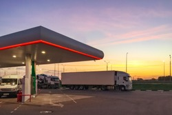 Truck white color and different cars is in parking lot of fueling station. Servicing of cars in evening or in morning time. 24-hour service. Empty place for text.
