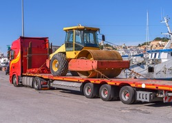 Truck with a long trailer platform for transporting heavy machinery load a 20 ton road roller