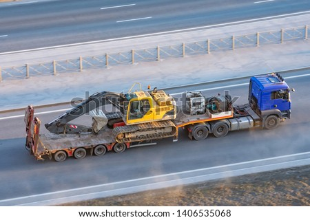 Truck with a long trailer platform for transporting heavy machinery, loaded crawler excavator with bucket. Highway transportation #1406535068
