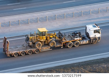 Truck with a long trailer platform for transporting heavy machinery, loaded tractor with a bucket. Highway transportation #1373217599