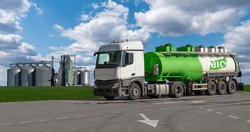 Truck with a tank with the inscription BIO on the background of silos. Biofuel concept.