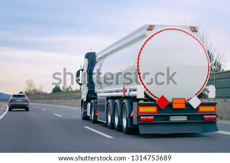 Truck with cistern on road. Trucker on highway. Lorry doing logistics work. Semi trailer with driver. Big cargo car. Freight delivery. Transport export industry. Container with loaded goods