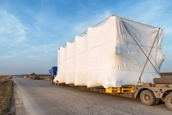 Truck with large oversized cargo on rural road. Industrial wide angle landscape