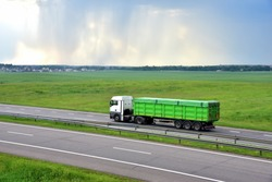 Truck with tipper semi trailer driving along highway on the green agriculture field background. Modern Dump Semi-Trailer Rear Tipper Truck Trailer. Goods Delivery and Services and Transport logistics