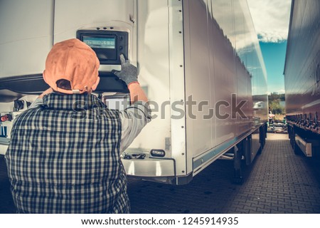 Trucker Adjusting Temperature in the Refrigerated Semitrailer. Transportation Industry Theme.