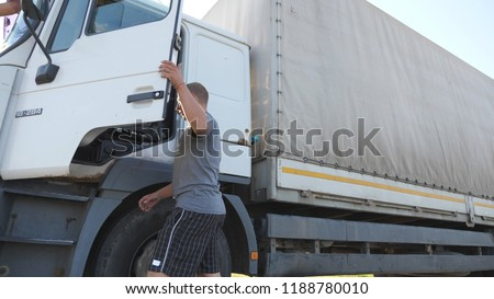 Trucker opens the door and sits down in his parked truck with a trailer. Driver continues the journey after stopping. Slow motion Close up.