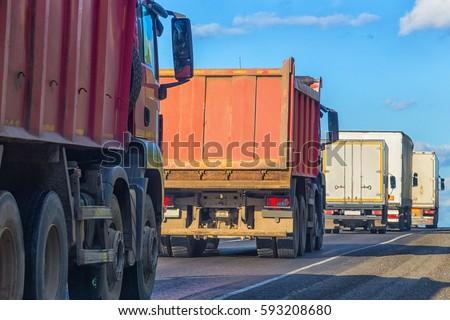 trucks and dump trucks go on highway in sunny day