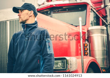 Trucks and Land Transport Industry Theme. Caucasian American Semi Truck Driver in Front of His Heavy Duty Lorry.
