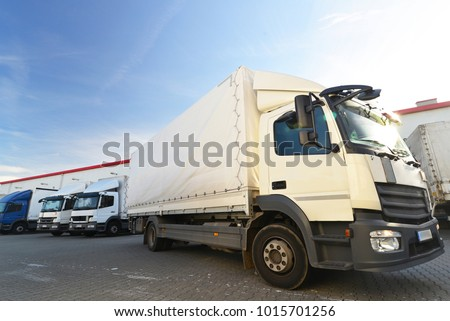 trucks are loaded with goods at the depot in a shipping company #1015701256
