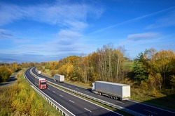 Trucks driving on the asphalt highway in the countryside with trees in autumn colors
