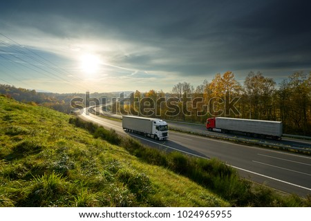 Trucks driving on the highway turning towards the horizon in an autumn landscape with sun shining through the clouds in the sky #1024965955