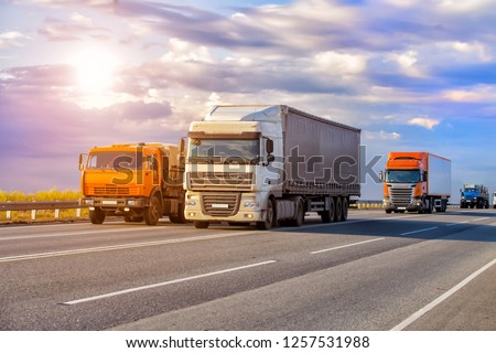 trucks goes on highway in evening on sunset #1257531988
