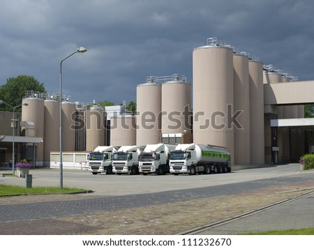 trucks in front of some large silos belonging to a milk powder factory