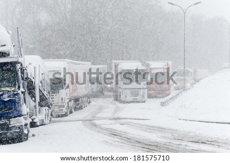 Trucks stopped on a highway during heavy snow storm