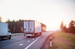 Trucks with a semi-trailer of 20 tons and a truck with a mass of 3.5 tons are transporting cargo on an evening road. Business in cargo transportation, freight price. Copy space for text, industry