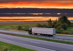 Trucks with Semi-trailer driving on highway on sunset background. Goods Delivery. Services and Transport logistics. Lorry driven