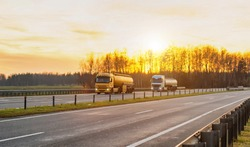 Trucks with semi-trailers in tanks transport fuel, lubricants, gasoline and diesel fuel on the highway against the backdrop of a sunny sunset, copy space for text