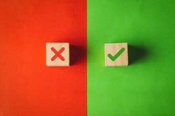 True and false symbols, Yes or No on wood cubes on red and green background.
