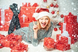 True Emotions. Young woman with Christmas present boxes in front of Christmas tree. New year eve girl. Beautiful Woman with Christmas box gif at Home. Christmas tree decorate at home