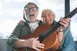 True happiness. Portrait of two sincere pensioners sitting together. Woman is cuddling man in cap while he is playing