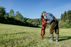 True love. A hunter stands on a sunny May day in his hunting area in an idyllic meadow valley and lovingly cuddles with his beautiful, shiny Irish Setter hunting dog.