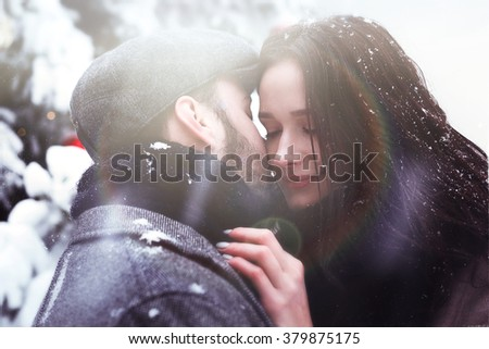 True love. Handsome man and pretty woman are posing outdoor on a snowy street #379875175