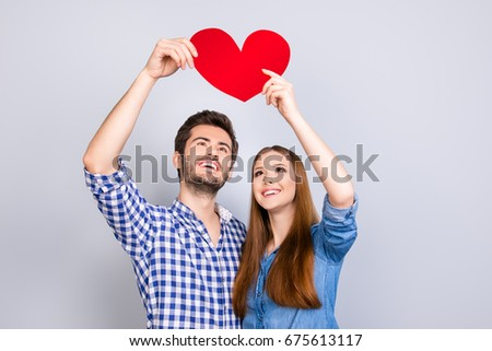 True love, trust, friendship, happiness, feelings, tenderness. Two young cute lovers are looking at the red heart and smiling, wearing casual outfits, on the pure background