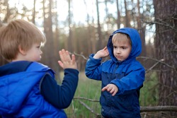 True men friendship, outing of crowed places, walking far from usual playground when lockdown is over. Two kids giving high five each other for greeting and support, outdoor summer lifestyle