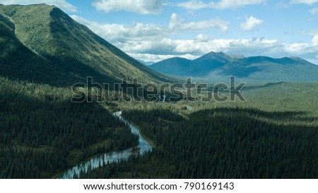 True wilderness. There is a river running through a remote Canadian forest, A cloudy but sunny day shows this untouched and uninhabited land. Very isolated from any sort of civilization.
