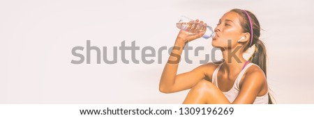 True wireless earbuds fitness woman drinking water bottle during fit workout outdoor on panoramic white background. Happy asian girl healthy lifestyle banner panorama. #1309196269
