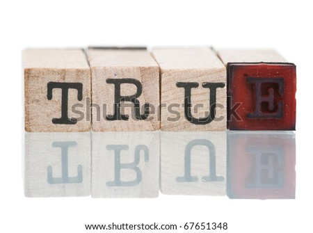 TRUE written with wooden blocks on white background