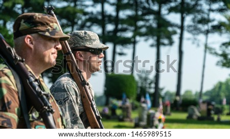 Trumbull County, Ohio/USA - May 28, 2018: Closeup Of Past And Present Military Soldiers Marching Side By Side During Memorial Day Parade With Rifle And Grave Site In Background. #1465989515