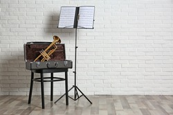 Trumpet, chair, case and note stand with music sheets near brick wall. Space for text