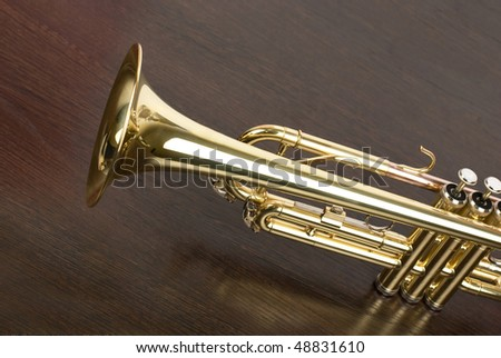trumpet closeup on brown wooden background - stock photo