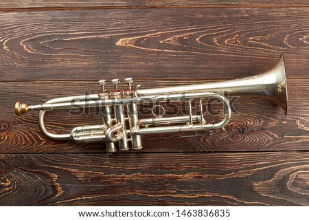 Trumpet on brown wooden background. Rusty trumpet on textured wooden surface. Classical music wind instrument. #1463836835