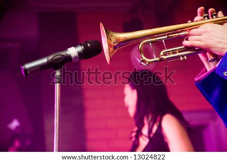 Trumpet player playing into microphone on a stage