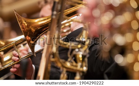 Trumpet professional player with symphony orchestra performing in concert on background. Сток-фото ©